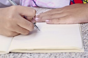 Children drawing on her note book.