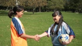 Two female athletes from opposing teams shaking hands