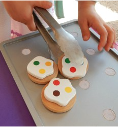 Using tongs to move objects on cookie sheet