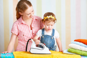 Little girl and mom ironing laundry together