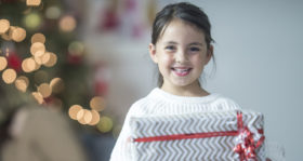 A little girl is happily standing with her Christmas present and is smiling and looking at the camera.