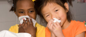 Little girls wipe their noses with tissues at school