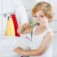 Little blond boy learning brushing his teeth