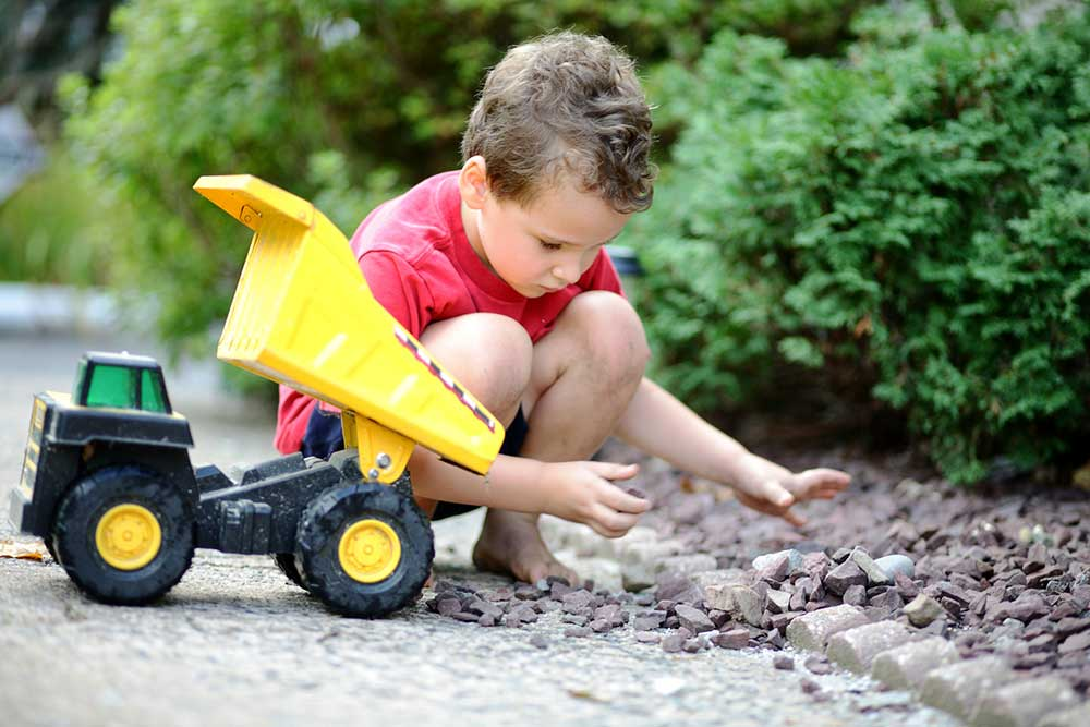Little boy playing with rocks and a toy truck