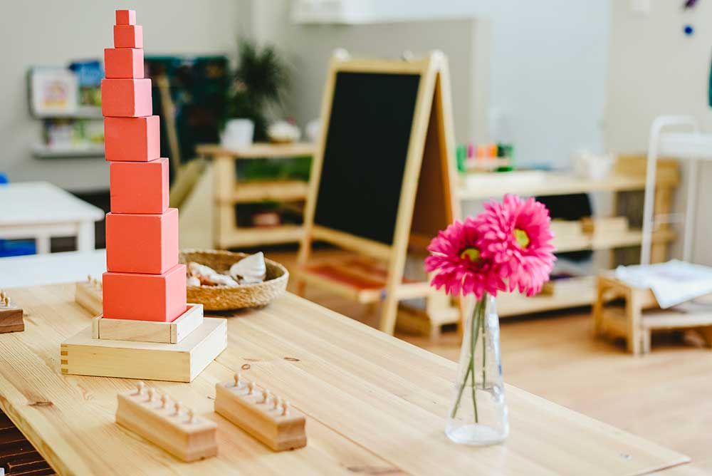 Craft room - wooden table with flowers in vase and stacked blocks